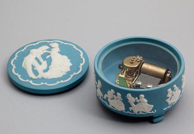 Cilinderspeelwerk in blauw porceleinen ronde doos met los deksel. Op de zijkant rondom 9 dansende figuren (man/vrouw) in kleding van eind 1800 ingekaderd door guirlandes. De doos staat op 3 porceleinen poten. Tekst onderop doos: 'D'Oyly Carte Opera Company The H.M.S. Pinafore Centennial Music Box Created by Franklin Porcelain FP 1978'. De melodie is I'm Called Little Buttercup.