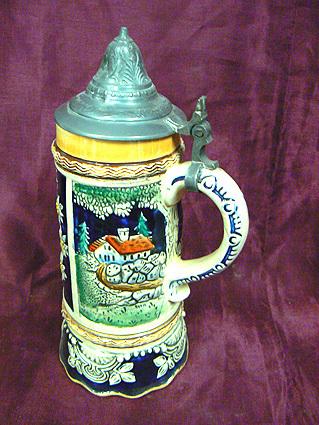 Bierpul van aardewerk met speelwerk uit ca. 1950, speelwerk gemaakt door Thorens Movement muziek 'Trink Bruderlein Trink'. Kleuren blauw en groen. Uurwerk gemaakt in Zwitserland. Bierpul met opschrift Kiel. Stadsgezicht Kiel, gedecoreerd met Edelweiss. Deksel gemaakt van tin.