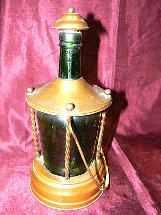 Fleshouder van koper waarin een fles van groen glas. Het optillen zorgt ervoor dat het speelwerk geaktiveerd wordt. Duitse makelij, datering 1950.