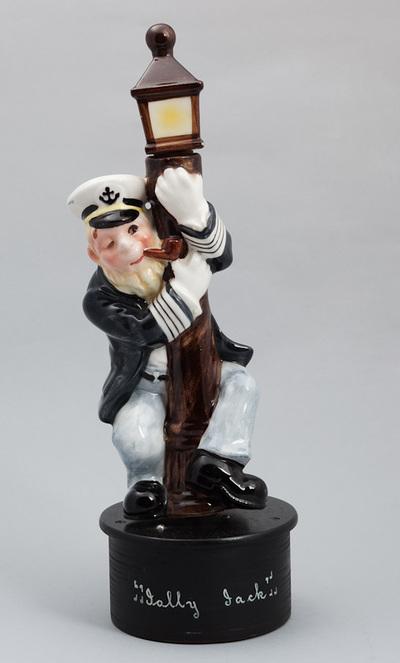 Beeld van aardewerk, voorstellende een dronken schipper zich vasthoudend aan een lantaarnpaal. Geheel op houten voetstuk met daarop de titel van het lied: Jolly Jack. Speelwerk opwinden door draaien van voetstuk. Datering 1940.
