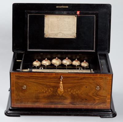 Fraaie cilinderspeeldoos, gemaakt omstreeks 1880. Het instrument heeft een toonkam met 70 tanden. Op de cilinder staan tien verschillende melodieën. De melodie van de toonkam wordt begeleid door zes bellen die aangetikt worden door hamertjes gedecoreerd met bijen. Het deksel van de houten kist vertoont inlegwerk met een ovalen medaillon en een bloemmotief. Aan de voorzijde een afbeelding van ingelegde bloemenranken met in het midden een ovalen gekroond medaillon en fantasiefiguren. Alle onderdelen zijn fraai en gedetailleerd uitgevoerd.