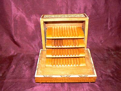 Sigarettendoos met cilinderspeelwerk, scharnierend deksel, 4 plateaus waarop in totaal 40 sigaretten kunnen liggen. Rondom ingelegd met ivoor en hout. Datering 1955.