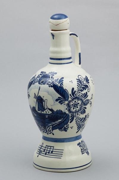 Schenkkan van Delfts aardewerk, afbeelding een Hollands landschap met molen en een muziekbalk. Speelwerk is van Reuge Zwitserland en wordt geactiveerd bij het optillen van de fles. Melodie: Edelweiss. Aan onderzijde het opwindmechanisme. Datering 1935-1950.