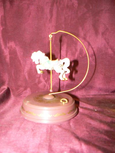 ChinaDraaimolen met speelwerk, melodie Waltz of the flower. Ronde schijf waarop opwindmechanisme, op de schijf een gebogen metalen staander waaraan een paard hangt. Deze draait wanneer de muziek speelt. De firma Enesco China bracht ieder jaar een speciale special uit van een mechanisch speelwerk. Datering 1992.