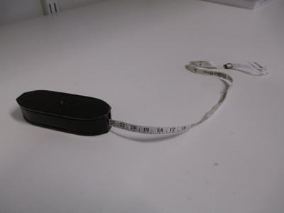 Kleur;zwarte ovale houder met B inscriptie, inhoud witte smalle centimeter 6 mm, merk; Stookt bruinkolen Briketten.