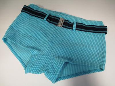 Kleur; blauwe zwembroek met verticale strepen in de stof, brede centuur in zwart en blauw met metalen gesp . Merk '' ANTRON . Maat 7.