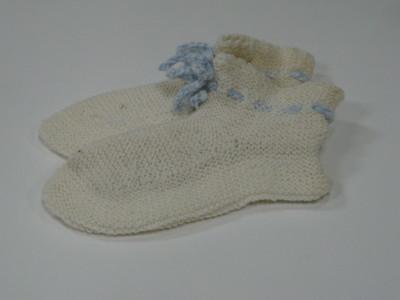 wit gebreide sokken in ribbelsteek met bovenrand een gehaakt boordje met blauw koord door gaatjes toer.