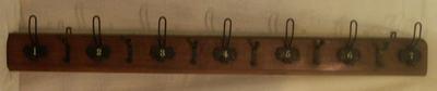 Houten kapstok met 7 ijzeren haken met eenvoudigere 6 tussenhaken; nummers 1 t/m 7 op de haken