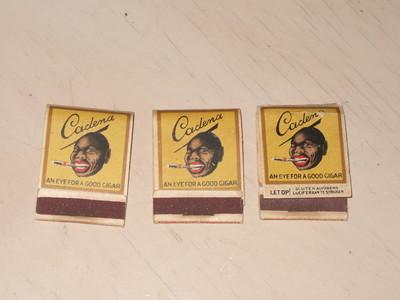 Lucifermapje van karton, vouwbaar. Gevuld met lucifers. Aan de voorzijde een strip voor het afstrijken van de lucifers. Opdruk van negerkop met sigaar en 'Cadena' op gele achtergrond.