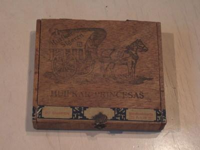 Vierkant kistje met scharnierend deksel voor 20 sigaren; Op buitenzijde deksel een afbeelding van een huifkar, getrokken door een paard.