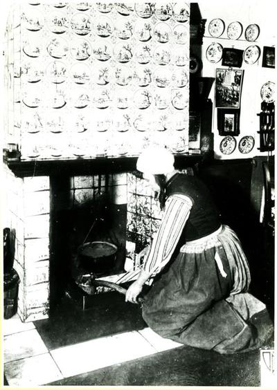 Vrouw in Marker dracht bij betegelde schouw