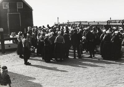 Groep mensen in Marker dracht bij de haven, 1943