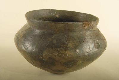 Urn van aardewerk, zwart glanzend, met schouderdeuken en kamversiering onder de schouderknik, ijzertijd.