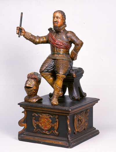 Prins Maurits (1567-1625) is als krijgsheer, in harnas en met commandostaf in de hand afgebeeld. De zittende houding op een taboeret gaat terug op de klassieke voorstelling van een triomferende generaal, in Nederland vooral bekend door het bronzen beeld van Willem van Oranje op zijn grafmonument in Delft. Dit werd in later tijd, en mogelijk ook door de maker van dit houten beeldje, wel aangezien voor prins Maurits, die meer dan zijn vader als veldheer bekend was. De gouden decoratie van het harnas refereert aan het vergulde pronkharnas dat de Staten-Generaal Maurits na de overwinning in de Slag bij Nieuwpoort schonken. De prins draagt sporen en de lichte beenbedekking in plooien moeten daarom laarzen zijn. Merkwaardig is dat het wapenschild van Maurits op de sokkel niet met het lint met de spreuk 'Honi soit qui mal y pense' van de Orde van de Kousenband is omgeven. Gezien het belang en de bekendheid van deze orde lijkt het onwaarschijnlijk dat de spreuk op een beeld van na 1613, het jaar dat de orde aan prins Maurits werd verleend, zou ontbreken. Tegen een datering vóór 1613 pleit echter de overeenkomst met het grafmonument in Delft, dat pas in 1622 werd voltooid.