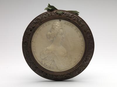 Dit portret van Mary II Stuart, afgebeeld met het gezicht naar rechts, in eigentijdse japon met decolleté en sieraden komt overeen met penningen waarop zij is afgebeeld, maar het kapsel is hier uitzonderlijk hoog. Gezien het omschrift 'MARIA. II. D. G. MAG. BRIT. FR. & HIB. REGINA' dateert dit stuk van na 1689, het jaar van de kroning van Willem III en Mary II. De toeschrijving aan Jean Cavalier (ca. 1650/60-1698/99) is gebaseerd op door hem gesigneerde ivoren portretmedaillons van Willem III en Mary II in Berlijn. Constantijn Huygens jr. schrijft in maart 1690 dat Willem III in het 'Coningin's Closet' in Kensington poseert voor Kneller en Cavalier en dat 'Cavalier, een Fransman, die portretten in ivoir maeckte en voorlede dynsd[ag] de Con[ing] oock soo geconterfeit had.' Het Berlijnse medaillon van Mary II is 1690 gedateerd. De medaillons waren waarschijnlijk een geschenk van Willem III aan zijn neef Frederik III, keurvorst van Brandenburg, ter gelegenheid van het verlenen van de Orde van de Kousenband. De overhandiging van ordetekenen vond in 1691 plaats. Dit stuk is gevat in een lijst van buxushout met gesneden bladrankenmotieven. Aan de bovenzijde van de lijst zijn twee gaatjes zichtbaar met daar doorheen een groen zijden lintje gestrikt.