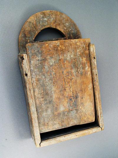 Een rechthoekig houten kistje met handvat en een schuif om de schooltas te openen. Centraal op de deksel de initialen: W B M .