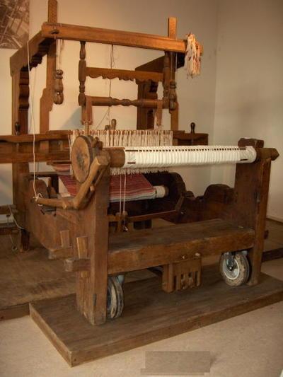 Houten weefgetouw voorzien van garen en geweven doek