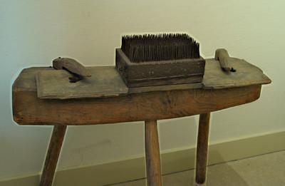 Model: lange plank, in het midden iets versmald. Op het middenstuk een blok hout, bekleed met ijzer en voorzien van pinnen.