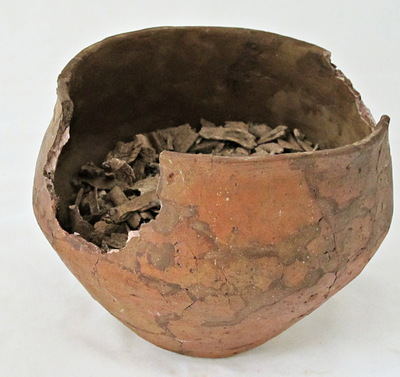 Klokbeker urn voor ongeveer een derde gevuld met crematieresten. Aan de bovenrand ontbreken twee stukken.