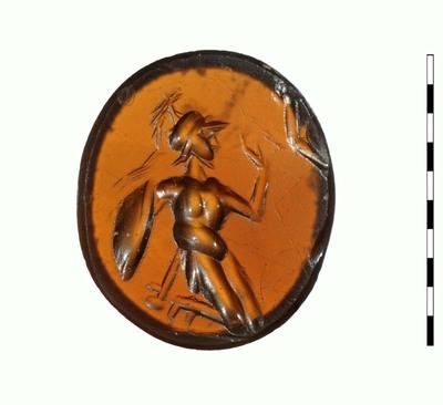 Gem, van gesneden steen (sarder), uit de Romeinse periode (Augusteïsch). Afgebeeld is een naakte, knielende man met een helm met helmbos op het hoofd. Hij houdt in zijn rechterhand een schild en hij heeft een zwaard bij zich. Rechtsboven een slang of een boomtak.