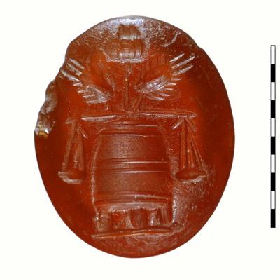 Gem, van gesneden natuursteen (karneool) uit de Romeinse periode (Augusteïsch). Afgebeeld is een aerarium (van Buchem noemt het een trog) op drie poten, waarin een papaverbol, geflankeerd door twee korenaren. Een weegschaal is opgehangen aan het aerarium.