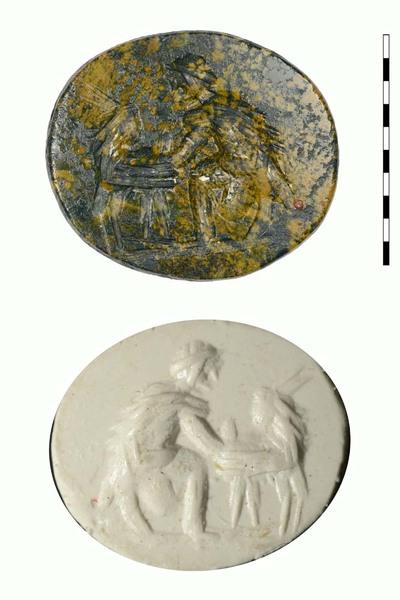 Gem, van natuursteen (heliotroop), uit de Romeinse periode. Afgebeeld is een geitenherder, die een geit aan het melken is, naar links gericht. Hij heeft een ruwe mantel om en hij melkt een geit die voor hem staat en de kop naar hem omdraait. Er is een grondlijn zichtbaar.