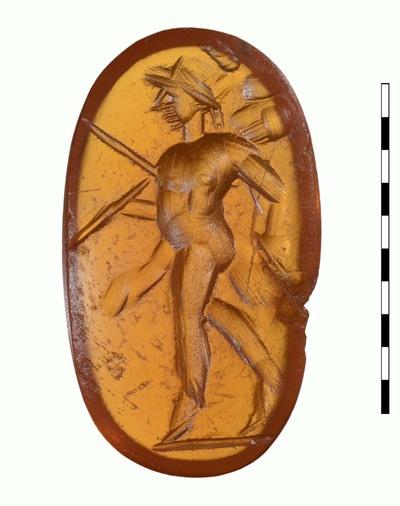 Gem, van natuursteen (karneool), uit de Romeinse periode. Afgebeeld is Mars (Pater), gehelmd en naakt op een sibligaculum rond de taille, die aan beide zijden van het lichaam zweeft. In zijn linkerhand draagt hij een speer, die schuin naar beneden wijst en de andere hand draagt een tropaion over de schouder.