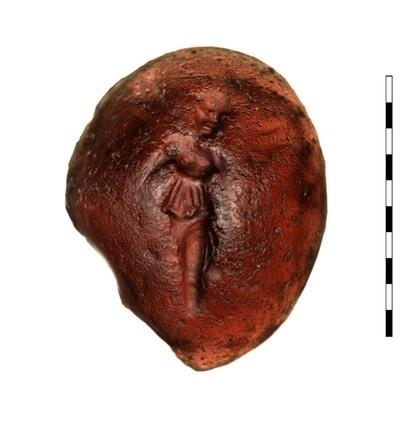 De gem, een gesneden, purperkleurige glasimitatie van amethyst, uit de Romeinse Republikeinse periode (Campaans/Hellenistisch-Republikeinse stijl). Afgebeeld is een godin (Victoria/Nike), gekleed in een chiton met bovenkleed. Twee vleugels (?), vermoedelijk een palmtak over haar schouder, maar het oppervlak is sterk afgesleten. Driekwart aanzicht. Dompierre spreekt van dansende vrouw.