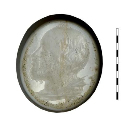 Gem van gesneden natuursteen (chalcedoon) uit de 17e-18e eeuw. Afgebeeld is een man, naar links gericht. De kruin van het hoofd en het voorhoofd zijn kaal; het haar is kort in de nek. De baard is kort.