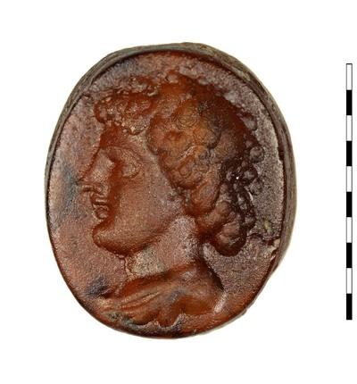 Gem van gesneden glas als imitatie van natuursteen (sarder) uit de Romeinse periode. Afgebeeld is een buste met draperie van een jonge neger. Het kapsel vertoont neerhangende krulletjes. De neus is recht, de lippen gedecideerd dun. Hij is naar links gericht.