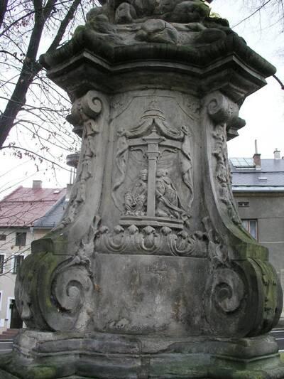 Štíty. Pilíř se sochou sv. Jana Nepomuckého. Podstavec s reliéfem Zpověď královny Žofie, záběr od S.