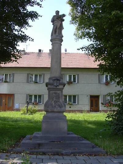 Rataje, sloup se sochou Panny Marie s Ježíškem na návsi před čp. 7, pohled od V
