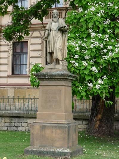 Jičín, ulice 17. listopadu, v parku před budovou ZŠ -  socha Jana Amose Komenského (celkový pohled, v pozadí čp. 109)