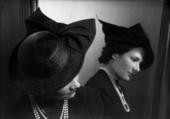 Ritratto di donna allo specchio con cappello e collana
