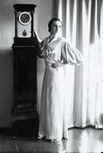 La signora Blasig in vestaglia accanto a un orologio a pendolo