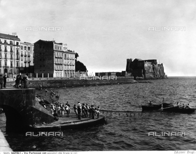 Fishermen at Via Partenope in Naples. In the background, Castel dell'Ovo.