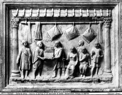Roman bas relief in marble depicting a cloth merchant's shop. Pillows hanging on a rod adorn the top of the piece.
