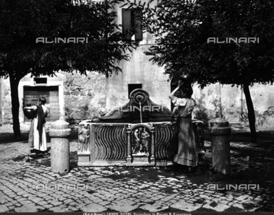 Two women drawing water from a fountain in Sutri. The fountain basin is probably a sculpted sarcophagus.