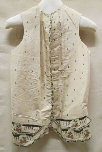 Vest (man) van crèmekleurige zijde met borduursel van strooimotiefjes in groene zijde en lovertjes op de voorpanden en knopen