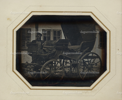 Image of a chariot, with the driver posing aside the chariot