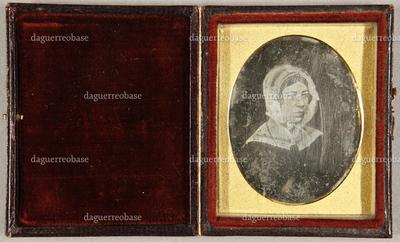 Ältere Frau mit weißer Haube und einem weißen Kragen, seitlich sitzend, Brustportrait.