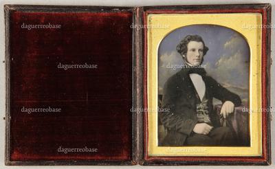 Junger Mann mit gelockten Haaren, am Tisch, auf dem ein Arm ruht, vor einem Wolkenhintergrund sitzend,, Halbfigur.