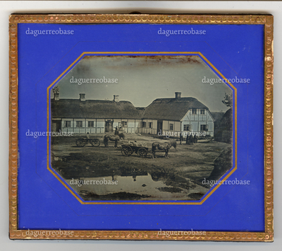 Outside scenery, horses and charriots, several people, posing before two large farmhouses, covered wit straw roofs