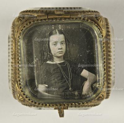 Junges Mädchen mit Korkenzieherlocken und langer Halskette am Tisch sitzend, ein Arm darauf ruhend, Halbfigur. Die Daguerreotpie ist im Deckel eines Kästchens aus Glas und Metall montiert.
