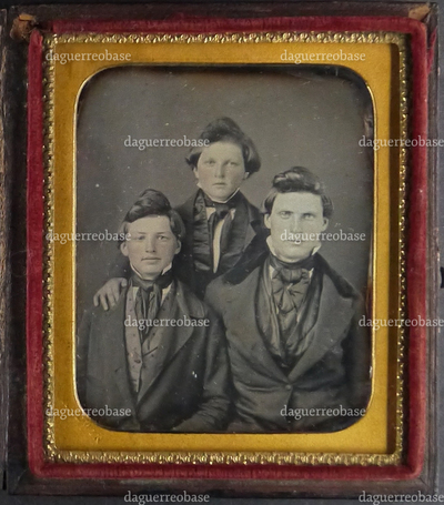 three boys, probably brothers, with same strange haircut, two boys sitting, one standing in the middle behind the two sitters