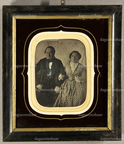 Älteres Ehepaar, er leicht nach vorn gebeugt, sie hat sich bei ihm eingehakt, Dreiviertelfigur, teilkoloriert.