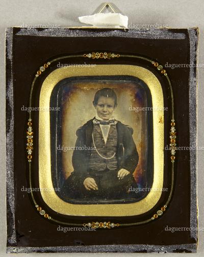Junge im Mantel sitzend, an seiner Jacke hängt eine lange Uhrenkette, Dreiviertel