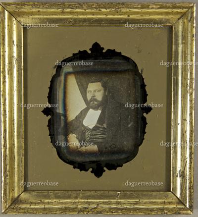 Mann mit Vollbart, seitlich neben einem Tisch sitzend, auf dem sein Zylinder und ein Arm ruht, im Hintergrund ein zur Seite geraffter Vorhang, Halbfigur.