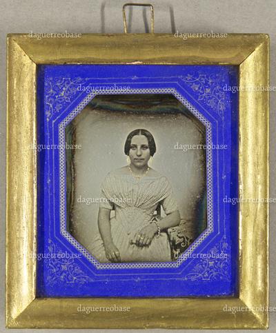 Junge Frau mit Ohrringen und Halskette am Tisch sitzend, ein Arm darauf ruhend, Halbfigur, teilkoloriert.