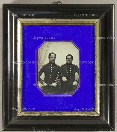 Zwei Offiziere  mit weißen Handschuhen nebeneinander sitzend, der links sitzende hält eine Peitsche in der Hand, der andere hat sich bei ihm eingehakt, Halbfigur.